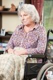Mujer mayor infeliz que se sienta en silla de ruedas Imagenes de archivo