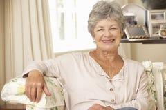 Mujer mayor jubilada que se sienta en Sofa At Home Foto de archivo libre de regalías