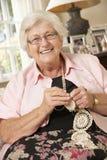 Mujer mayor jubilada que se sienta en Sofa At Home Doing Crochet fotografía de archivo