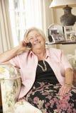 Mujer mayor jubilada que se sienta en Sofa At Home On Phone Fotos de archivo