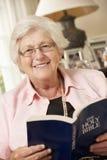 Mujer mayor jubilada que se sienta en Sofa At Home Reading Book Imágenes de archivo libres de regalías