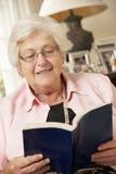 Mujer mayor jubilada que se sienta en Sofa At Home Reading Book Imagen de archivo