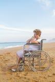 Mujer mayor lisiada en la playa Imagenes de archivo