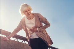 Mujer mayor menuda que sufre del dolor de estómago Imagenes de archivo