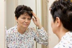 Mujer mayor morena que sostiene las lentes en el top de su cabeza y que mira meticuloso sí misma en el espejo fotografía de archivo
