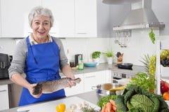 Mujer mayor o más vieja con el pelo gris que cocina en la cocina - fresca foto de archivo