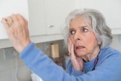 Mujer mayor olvidadiza con la demencia que mira en armario fotografía de archivo