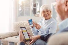 Mujer mayor optimista que muestra el tiempo app a su marido foto de archivo