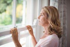 Mujer mayor pensativa que mira hacia fuera de la ventana Imágenes de archivo libres de regalías