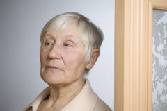 Mujer mayor pensativa que mira lejos por la puerta Fotografía de archivo