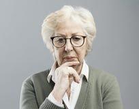 Mujer mayor pensativa que piensa con la mano en la barbilla imagenes de archivo