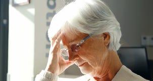 Mujer mayor pensativa que se sienta en silla en pasillo almacen de metraje de vídeo
