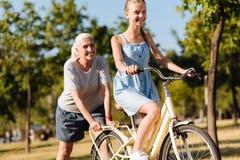 Mujer mayor positiva que enseña a su nieta que monta una bicicleta Fotos de archivo
