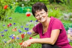 Mujer mayor positiva que se sienta entre las flores en un jardín Foto de archivo