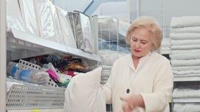 Mujer mayor preciosa que sonríe a la cámara, almohada de examen en tienda de muebles almacen de metraje de vídeo