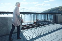 Mujer mayor preocupante que mira fijamente en alguna parte mientras que camina con las muletas Imagen de archivo