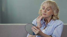 Mujer mayor preocupante que mira su reflexión en espejo, cirugía plástica, envejeciendo almacen de metraje de vídeo