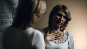 Mujer mayor presionada que mira la reflexión en el espejo, cáncer de piel, preocupaciones fotos de archivo