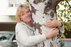 Mujer mayor que abraza el árbol de abedul Foto de archivo