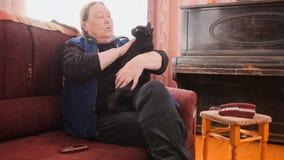 Mujer mayor que acaricia el gato negro Fotos de archivo