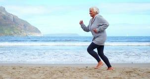 Mujer mayor que activa en la playa almacen de metraje de vídeo