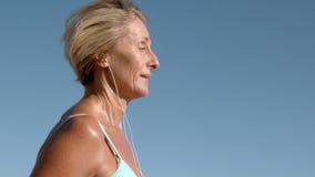 Mujer mayor que activa en un día soleado que escucha la música almacen de video