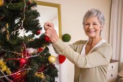 Mujer mayor que adorna el árbol de navidad Foto de archivo libre de regalías