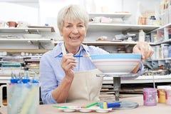 Mujer mayor que adorna el cuenco en clase de la cerámica Foto de archivo libre de regalías