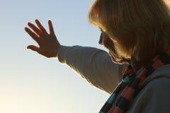 Mujer mayor que alcanza hacia fuera al sol Foto de archivo