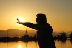 Mujer mayor que alcanza para el sol poniente Imagen de archivo libre de regalías