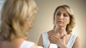 Mujer mayor que aplica la crema de alimentación en el cuello y la zona decollete, cuidado de la anti-edad almacen de video