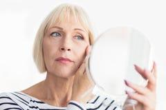 Mujer mayor que aplica la crema de cara, mirando el espejo fotos de archivo