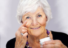 Mujer mayor que aplica la crema en su cara Imagenes de archivo