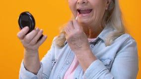 Mujer mayor que aplica lustre del labio delante del pequeño espejo, cosméticos antienvejecedores almacen de metraje de vídeo
