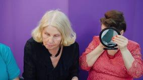 Mujer mayor que aplica maquillaje en espejo delantero de la cara el pequeño en escuela de la belleza Mujer madura dos que corrige almacen de metraje de vídeo