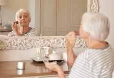 Mujer mayor que aplica maquillaje a su mejilla en un espejo Imagenes de archivo