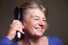 Mujer mayor que aplica su pelo con brocha Foto de archivo libre de regalías