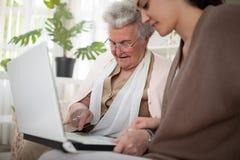 Mujer mayor que aprende cómo mecanografiar Imágenes de archivo libres de regalías