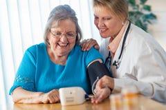 Mujer mayor que aprende de doctor utilizar la máquina de la presión arterial fotografía de archivo libre de regalías