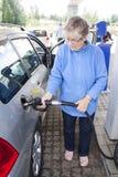 Mujer mayor que aprovisiona de combustible el coche Fotografía de archivo