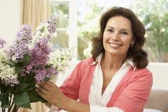 Mujer mayor que arregla las flores Foto de archivo libre de regalías