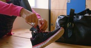 Mujer mayor que ata el cordón en el vestuario 4k del gimnasio almacen de metraje de vídeo