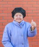 Mujer mayor que aumenta el pulgar para arriba Fotos de archivo