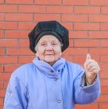 Mujer mayor que aumenta su pulgar para arriba Imágenes de archivo libres de regalías