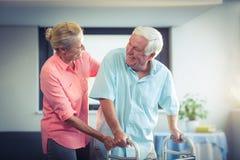 Mujer mayor que ayuda al hombre mayor a caminar con el caminante imagen de archivo libre de regalías