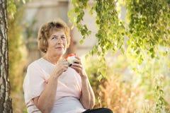 Mujer mayor que bebe de una taza debajo del abedul Imagen de archivo libre de regalías