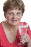 Vidrio de consumición de la mujer mayor de un agua mineral Imagen de archivo