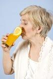 Mujer mayor que bebe el zumo de naranja fresco Foto de archivo
