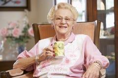 Mujer mayor que bebe la bebida caliente Imagen de archivo libre de regalías