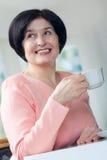 Mujer mayor que bebe un café Imagenes de archivo
